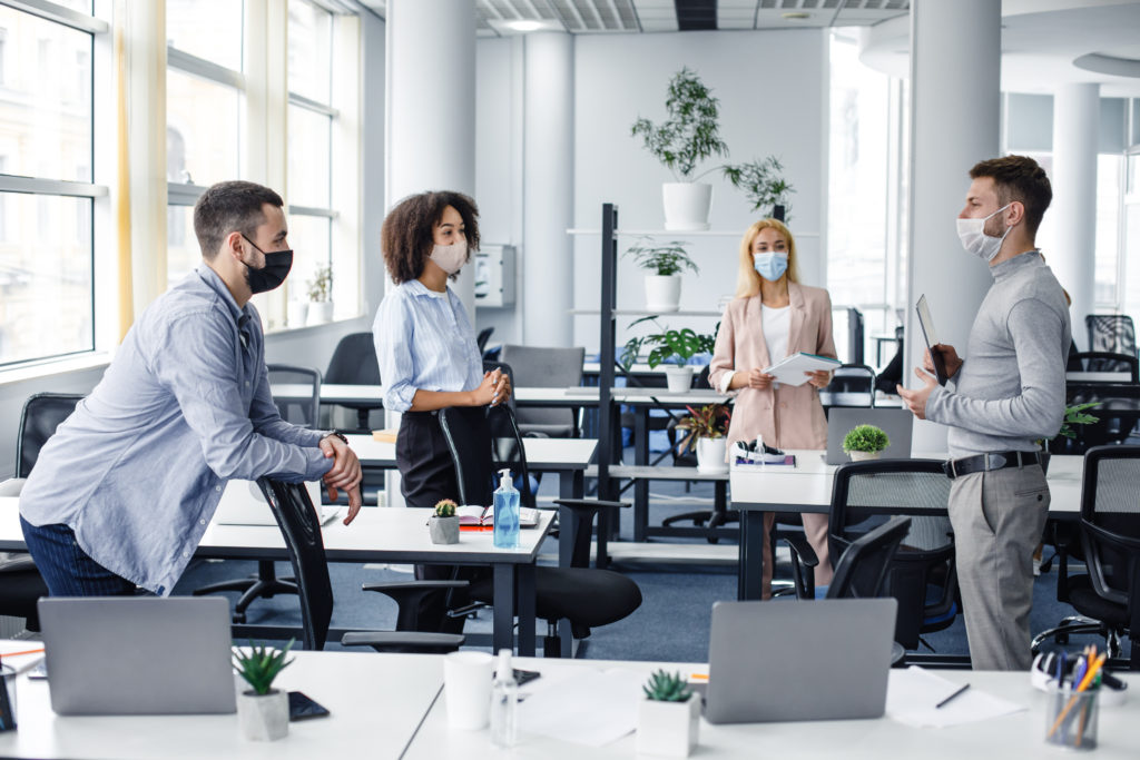 Modern team meeting, group work and social distancing. Manager with tablet speaks with workers in protective masks in interior of modern office with gadgets during coronavirus epidemic, free space